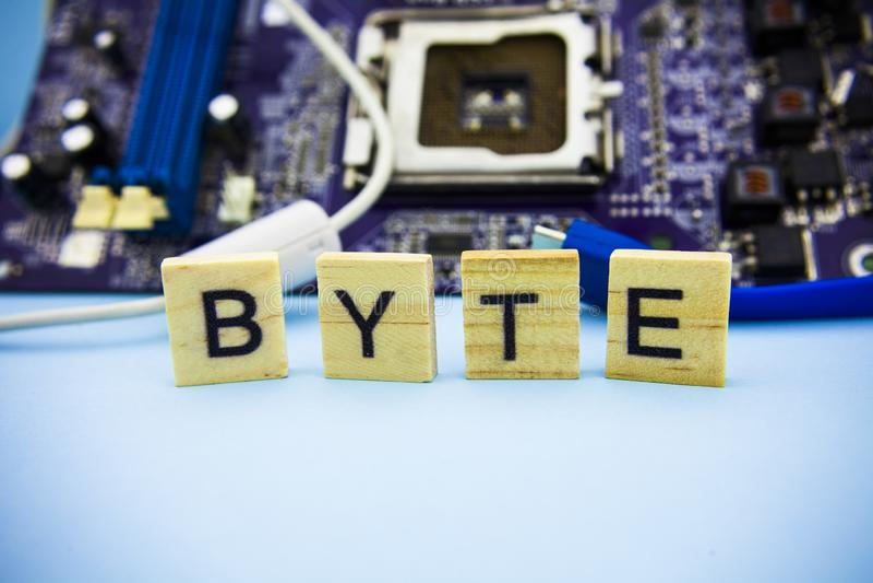 BYTE da palavra nos blocos de madeira com fundo do mainboard dos computadores Fundo da tecnologia da informação com mainboard fotos de stock