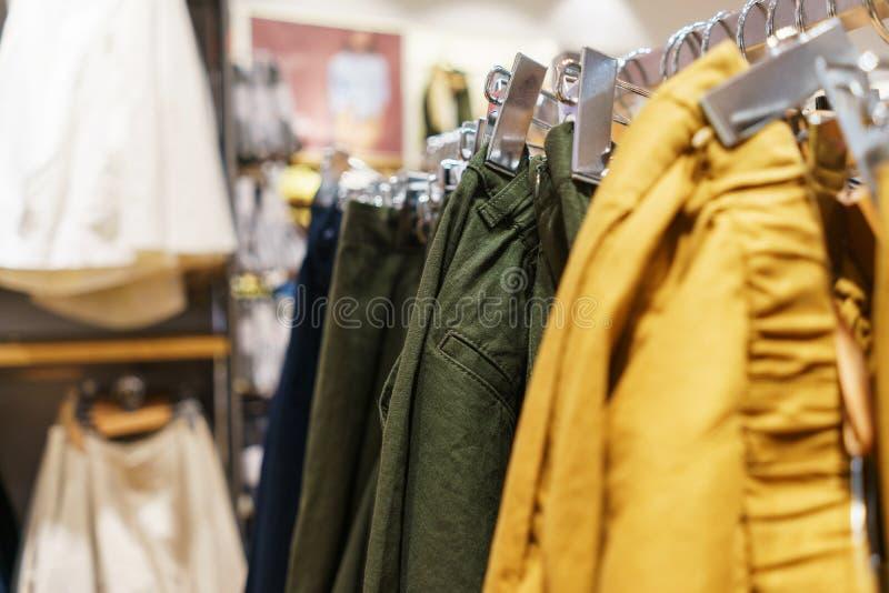 Byxa, en tröja och en hoodie på en hängare i ett modelager för ungdom arkivfoto