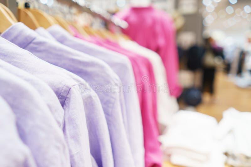 Byxa, en tröja och en hoodie på en hängare i ett modelager för ungdom arkivbild