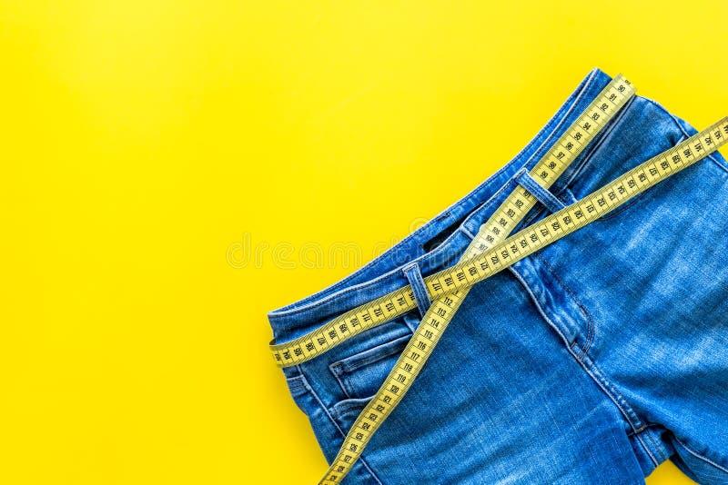 Byxa med att mäta bandet för viktförlust och sportbegrepp på gult utrymme för bästa sikt för bakgrund för text royaltyfria foton
