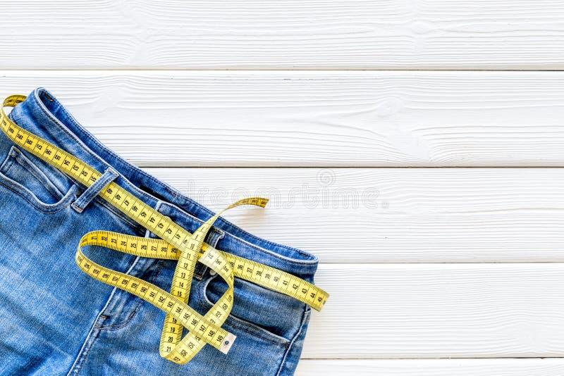 Byxa med att mäta bandet för viktförlust och sportbegrepp på vitt träutrymme för bästa sikt för bakgrund för text arkivbilder