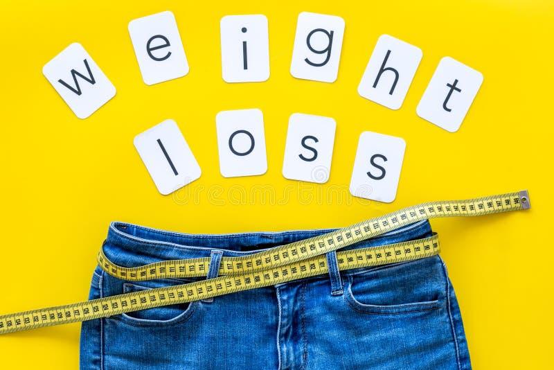 Byxa med att mäta det band- och för viktförlust begreppet för sportbegrepp på bästa sikt för gul bakgrund royaltyfri bild