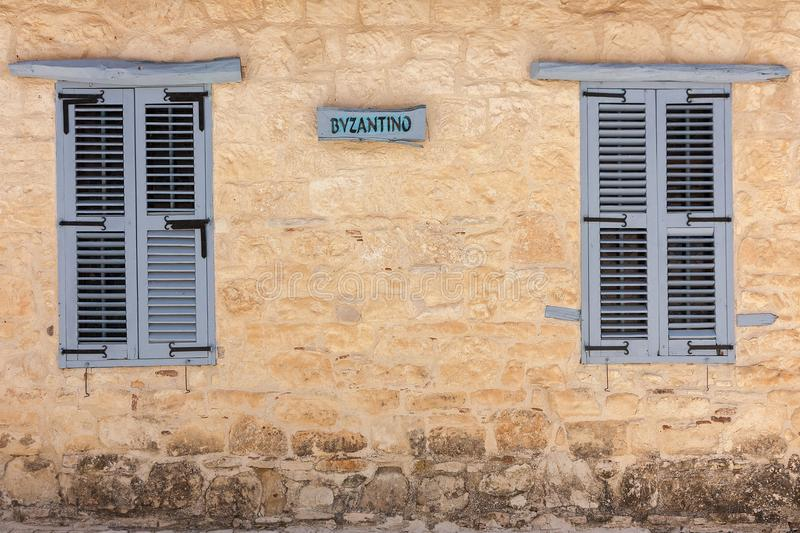 Byzantine wall with two blue old style windows, heritage home in Paphos, Cyprus royalty free stock images