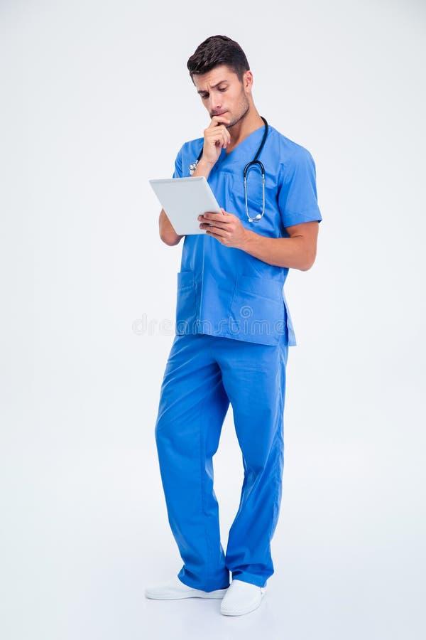 Cálculo masculino pensativo de la tableta de la tenencia del doctor fotografía de archivo