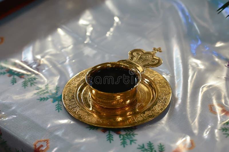 Cálice brilhante bonito dourado com vinho no altar da igreja, acessórios para a união das noivas foto de stock royalty free