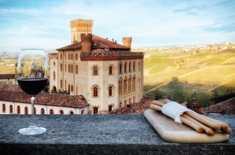 Cálice do vinho com palitos e o castelo de Barolo Itália fotos de stock royalty free