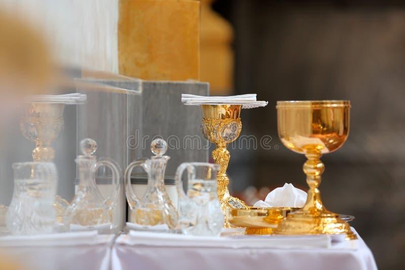 Cálice dourado no altar e nas ampolas com vinho e água antes da massa foto de stock royalty free