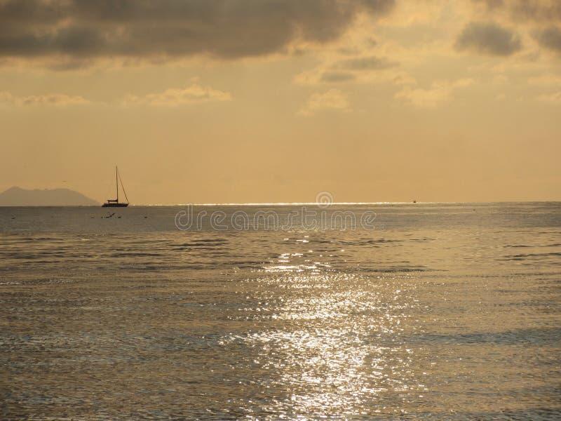 Cálida puesta de sol en el mar con velero y isla Gorgona en el horizonte Vista desde la ciudad de Livorno Toscana, Italia fotos de archivo libres de regalías