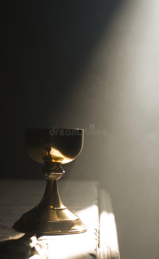 Cáliz del oro en altar con un rayo de la luz divina imagen de archivo