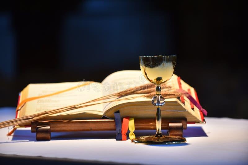 Cáliz y libro de oración abierto foto de archivo