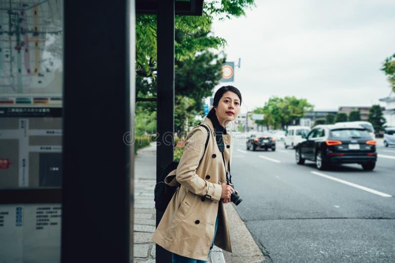 Cámara asiática de la tenencia de la mujer del viaje en la parada de la tranvía foto de archivo