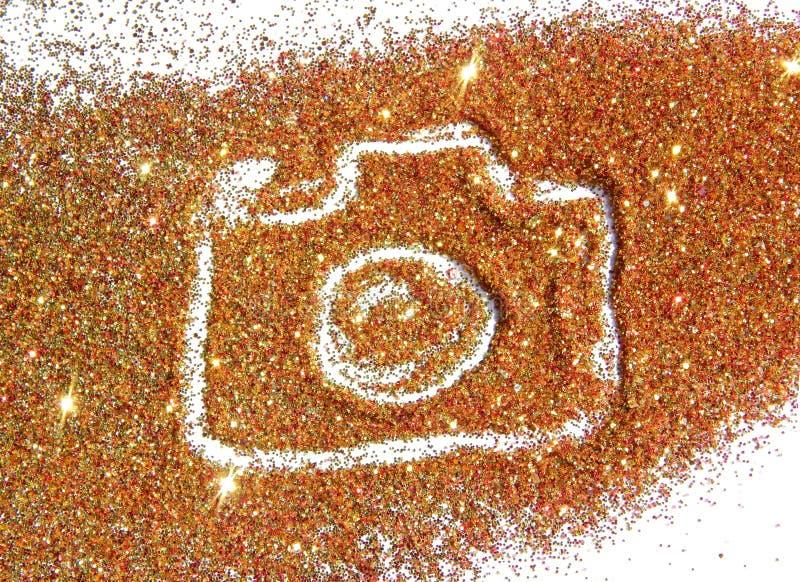Cámara borrosa de la foto en chispa de oro y roja del brillo en el fondo blanco fotografía de archivo libre de regalías
