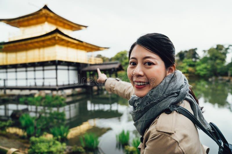 Cámara de la cara de la chica joven que muestra el pabellón de oro foto de archivo libre de regalías