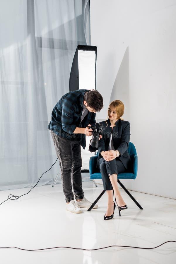 cámara de la demostración del fotógrafo a la mujer joven hermosa foto de archivo