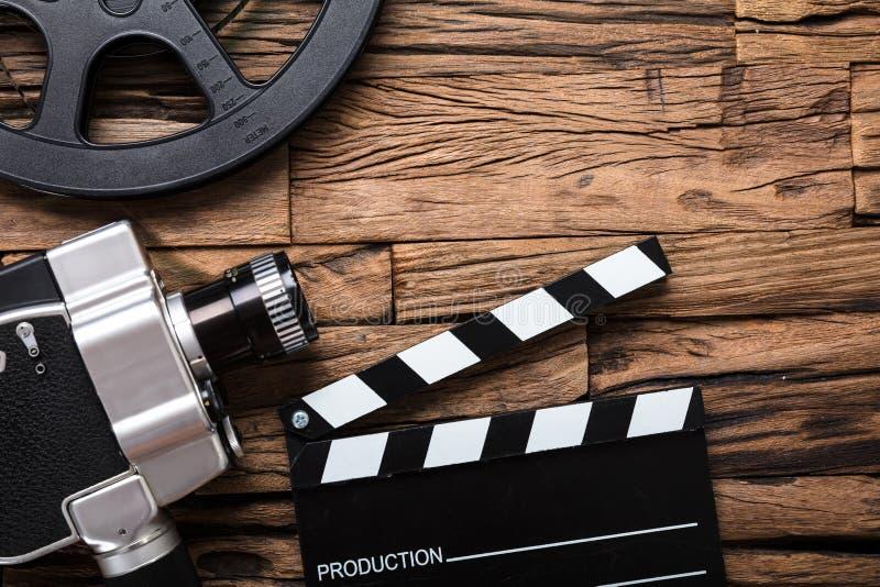 Cámara de película con el rollo de película y tablero de chapaleta en la madera fotos de archivo libres de regalías