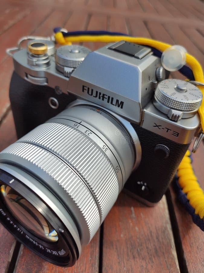 Cámara de plata y negra del vintage de Fujifilm con la correa de cuero marrón en la tabla de madera Copie el espacio para el text imagen de archivo