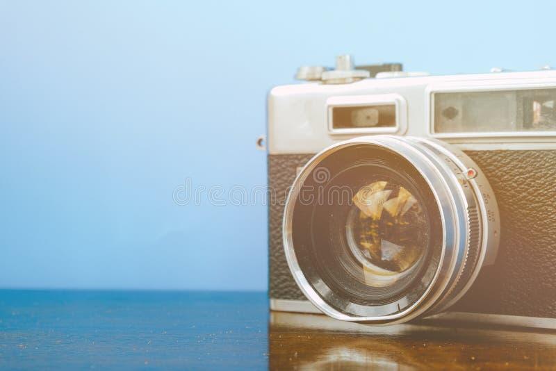 cámara del vintage en el escritorio de madera sobre fondo azul con efecto retro del color imagen de archivo