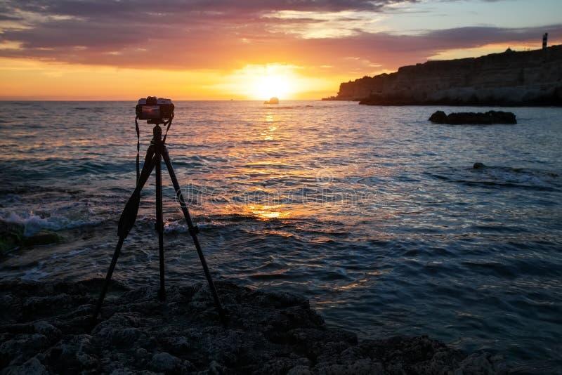 Cámara en un trípode en la playa del mar durante una puesta del sol ardiente imagen de archivo libre de regalías