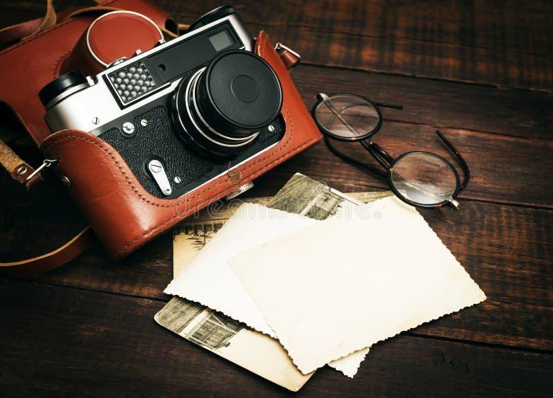 Cámara fotográfica retra y algunas fotos viejas en fondo de madera de la tabla fotos de archivo libres de regalías