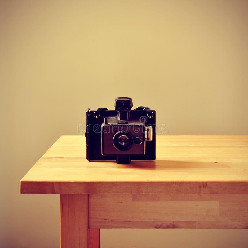 Cámara instantánea vieja en una tabla, con un efecto retro foto de archivo libre de regalías