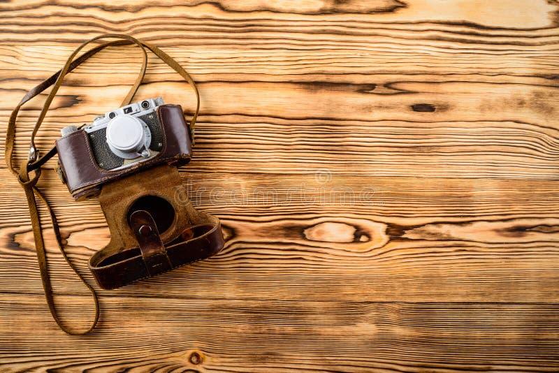 Cámara pasada de moda del viejo vintage retro en el caso de cuero en de madera imagen de archivo