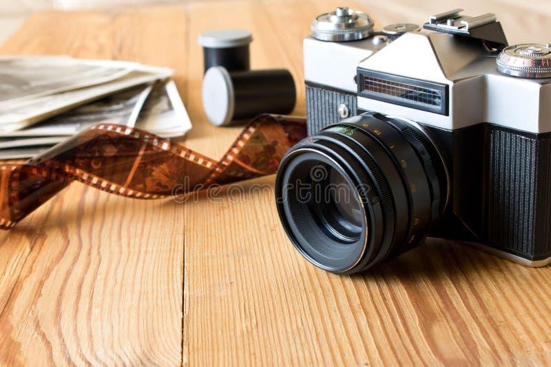 Cámara, película y fotos viejas del vintage en la tabla de madera fotos de archivo libres de regalías