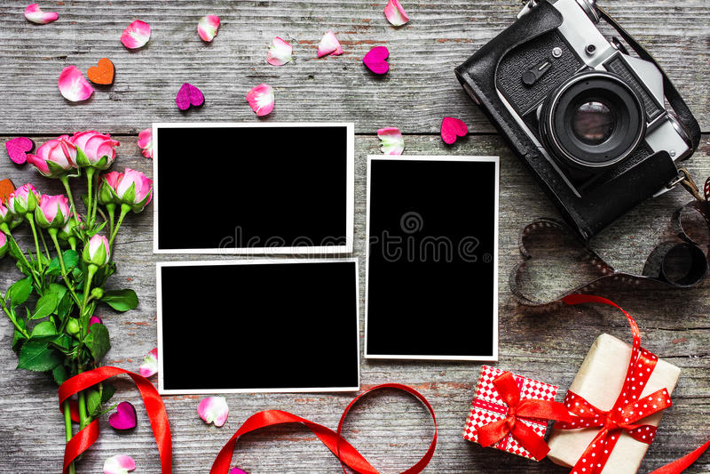 Cámara retra del vintage con los marcos en blanco de la foto y las rosas rosadas imagenes de archivo