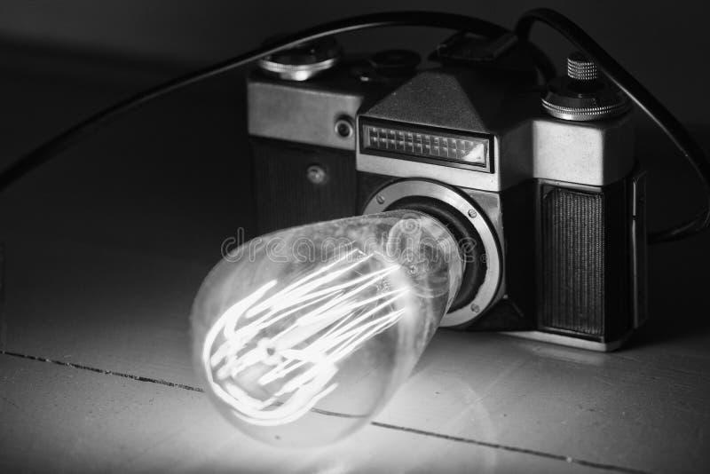 Cámara retra, lámpara de Edison, desván imagen de archivo