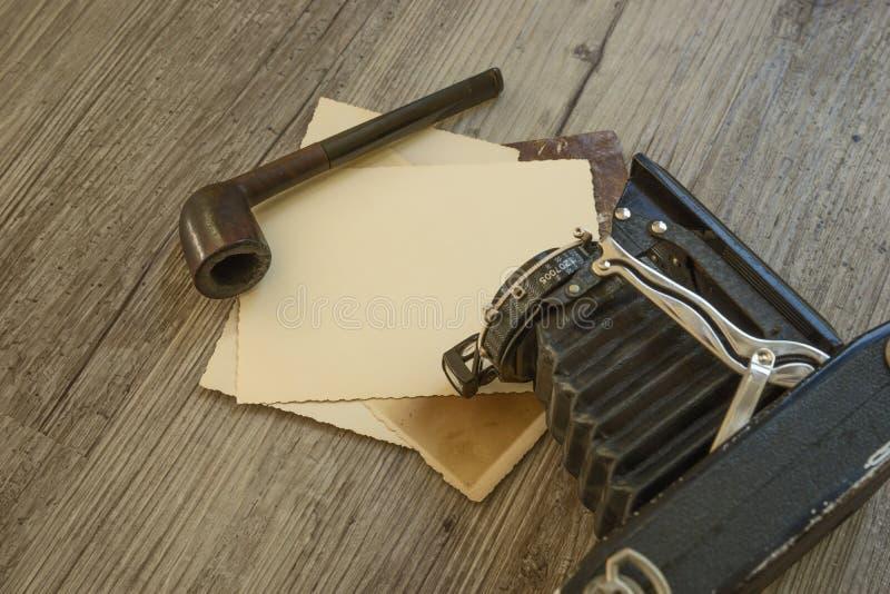 Cámara retra vieja con el tubo de tabaco en el tablero de madera fotografía de archivo libre de regalías