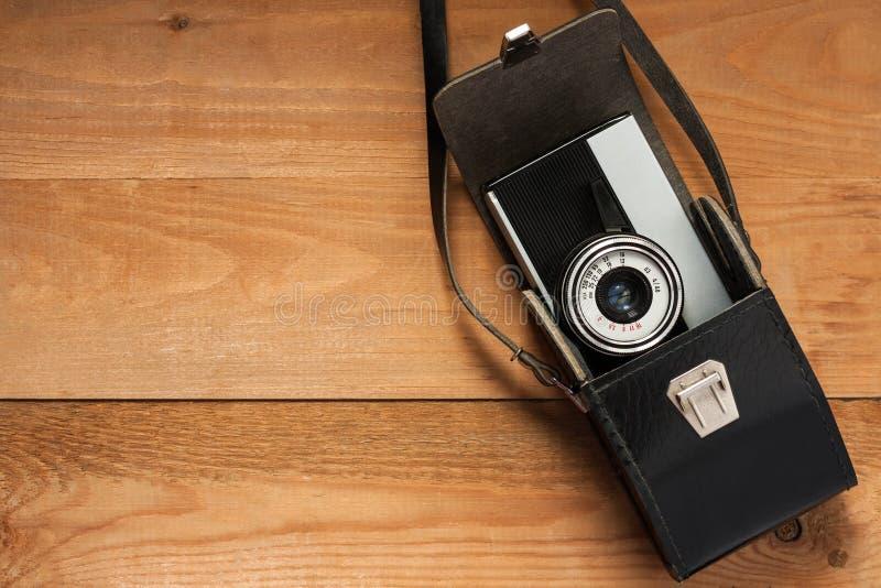 Cámara retra vieja del vintage en bolso de cuero negro en el tablero de madera Co imagen de archivo
