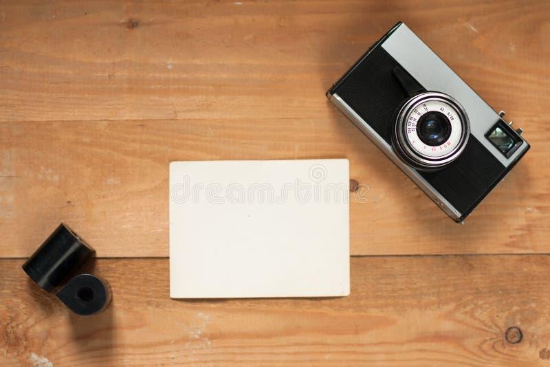 Cámara retra vieja, película y lista blanca en el tablero de madera de Brown fotos de archivo
