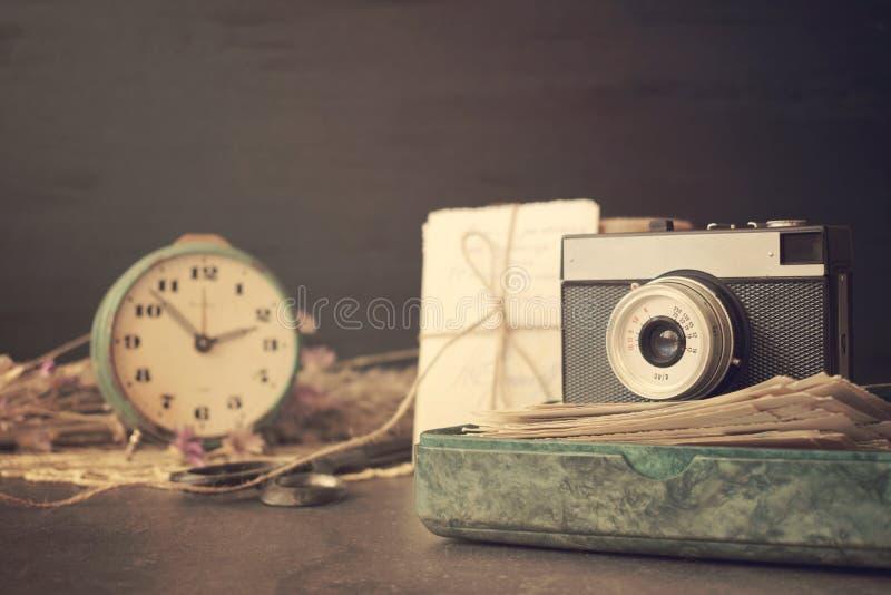 Cámara vieja retra con la pila de fotos, de letras, de caja de la malaquita y de relojes de la antigüedad en fondo de madera Memo foto de archivo