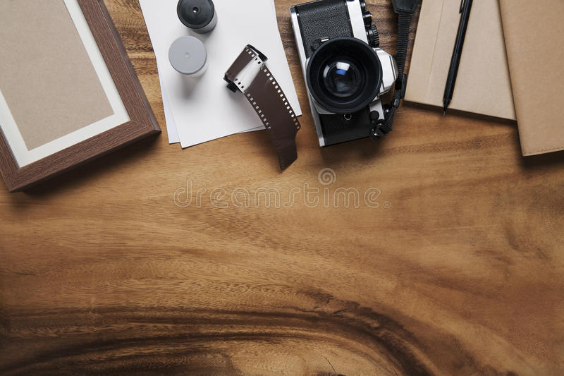 Cámara y fuentes, marcos en blanco de la foto en la tabla de madera imagenes de archivo