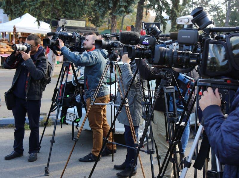 Cámaras de vídeo del fotógrafo y en la rueda de prensa fotografía de archivo