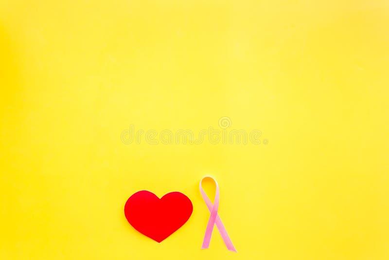 Cáncer de pecho Concepto del Mammalogy Cinta rosada simbólica cerca de la muestra del corazón en el espacio amarillo de la opinió foto de archivo libre de regalías