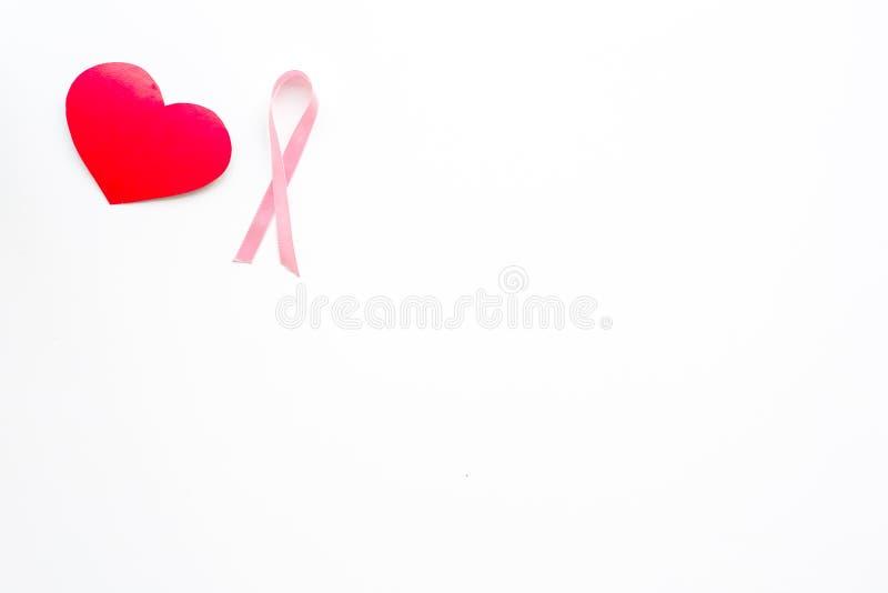 Cáncer de pecho Concepto del Mammalogy Cinta rosada simbólica cerca de la muestra del corazón en el espacio blanco de la copia de imagen de archivo