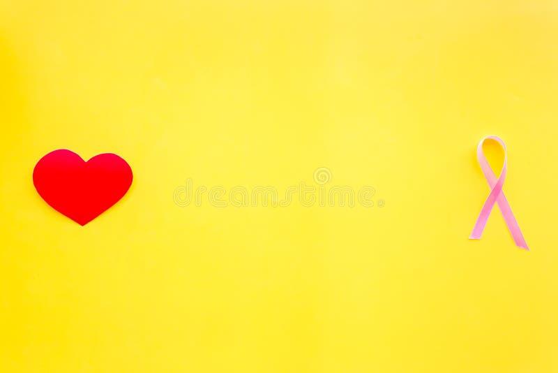 Cáncer de pecho Concepto del Mammalogy Cinta rosada simbólica cerca de la muestra del corazón en espacio amarillo de la copia de  imágenes de archivo libres de regalías