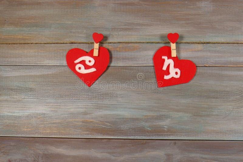 Cáncer y Capricornio muestras del zodiaco y del corazón Parte posterior de madera imagen de archivo libre de regalías