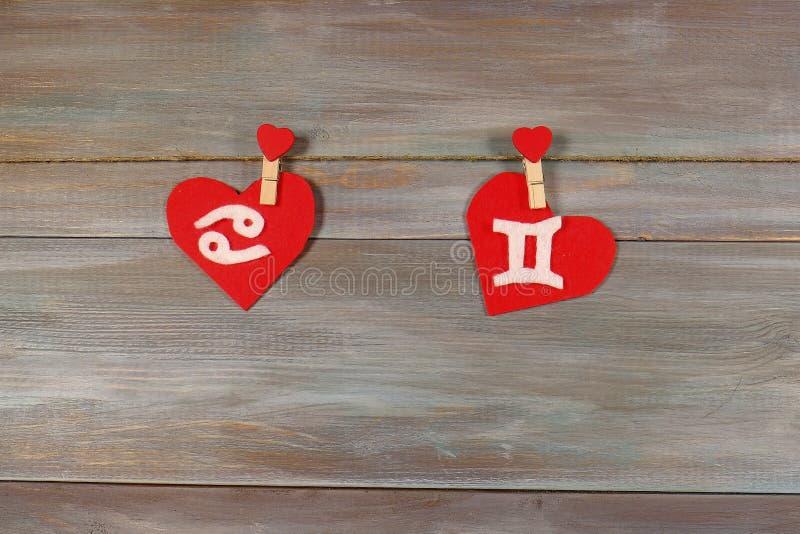 Cáncer y gemelos muestras del zodiaco y del corazón Backgrou de madera fotografía de archivo