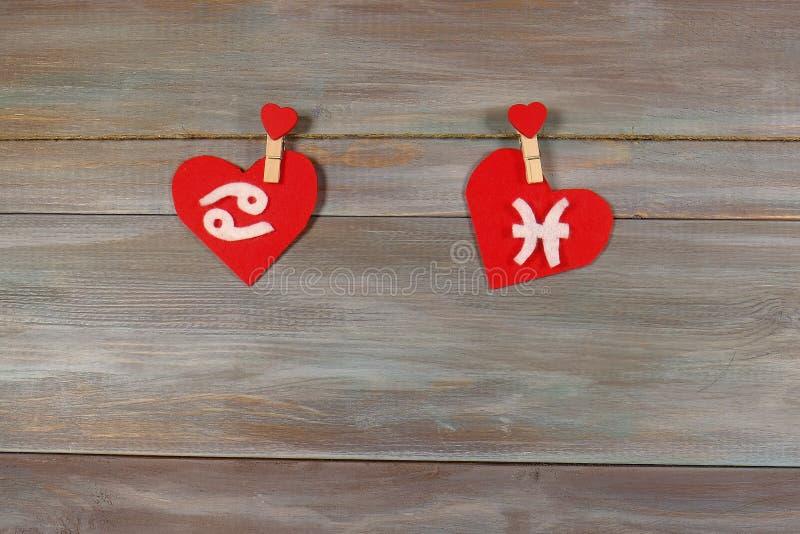 Cáncer y pescados muestras del zodiaco y del corazón Backgroun de madera imagen de archivo