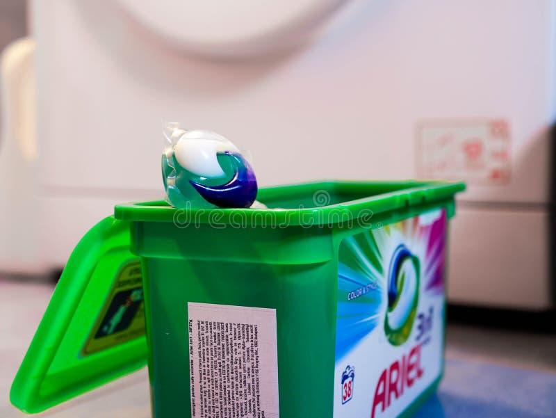 Cápsula detergente líquida de Ariel delante de una lavadora imagen de archivo