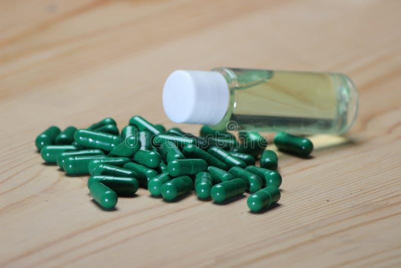 Cápsula verde com óleo erval na garrafa imagem de stock royalty free