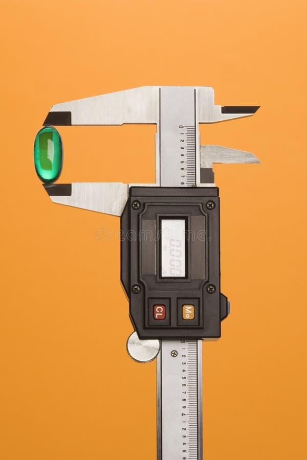 Cápsula verde no compasso de calibre. Isolado foto de stock royalty free