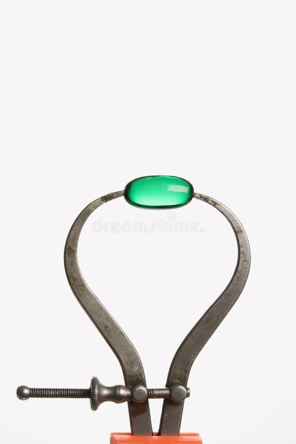 Cápsula verde no compasso de calibre. Isolado foto de stock