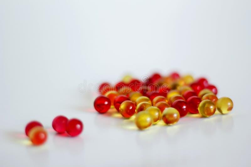 cápsulas amarelas e vermelhas com vitamina a e E fotos de stock