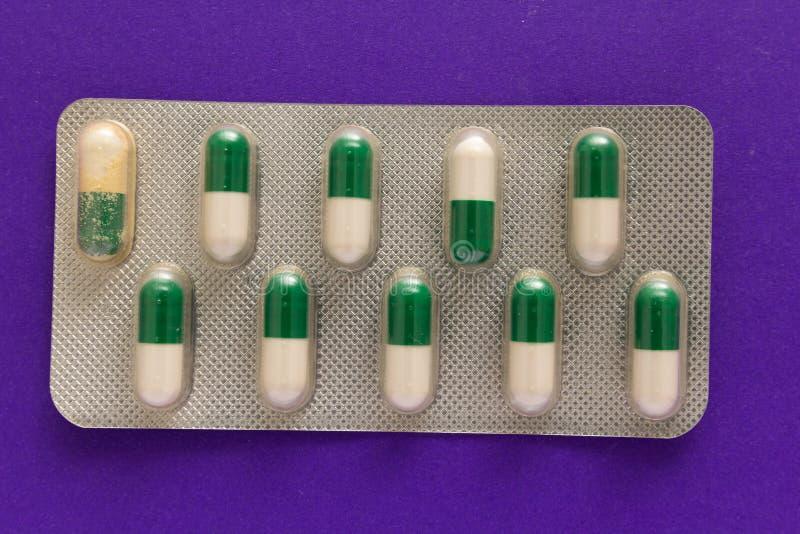 Cápsulas blancas y verdes expiradas en caja de la medicina Píldoras sobre pur fotos de archivo