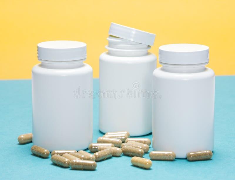 Cápsulas dispersadas com os frascos plásticos brancos imagem de stock