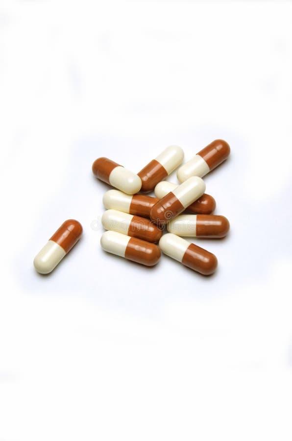 Cápsulas dispersadas de la píldora en el fondo blanco fotografía de archivo