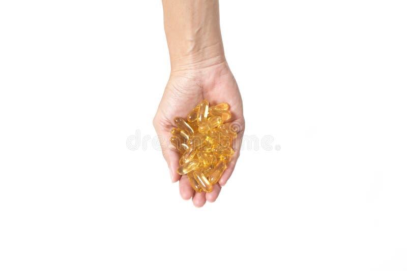 Cápsulas do óleo de peixes na mão fêmea imagem de stock