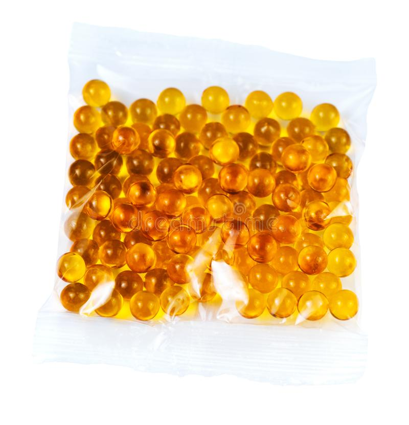 Cápsulas esféricas anaranjadas de la bola de aceite de pescado en la bolsa de plástico aislada en el fondo blanco foto de archivo libre de regalías